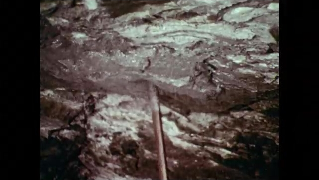 1970s: Man rams metal rod into ceiling of mine tunnel. Man lifts long pneumatic drill to ceiling and drills. Man pulls drill down and another man replaces large bit.