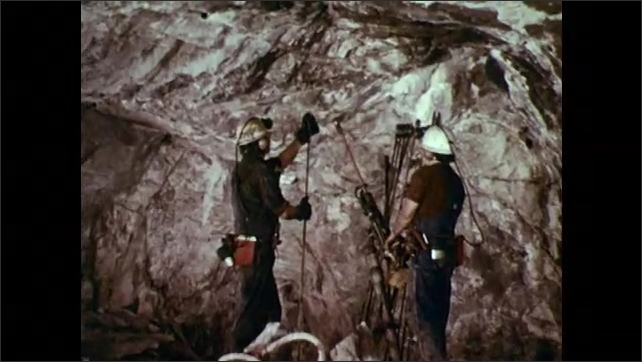 1970s: Man presses pneumatic drill into ceiling of mine tunnel. Man prepares bits to be used in drill. Man changes bit in drill. Man shoves rod into ceiling.
