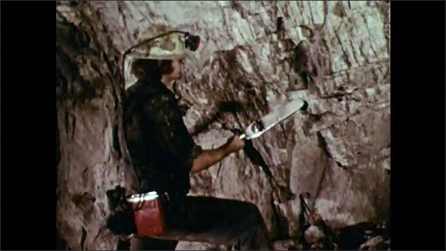 1970s: Man uses drill to insert rod and fastener into wall of mine tunnel. Man uses large ratchet to tighten bolt in wall. Gauge measures ratchet pressure.