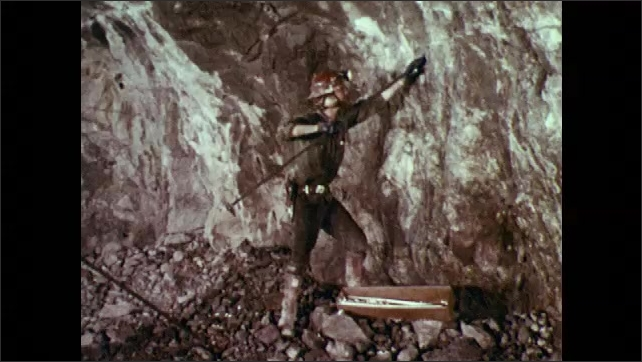 1970s: Man inserts tube into wall in mine tunnel, then uses metal rod to attach to it and pneumatic drill.