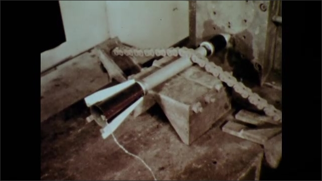1950s: Man sets up camera.  Small rocket secured to table by chain.  Man leaves room and closes heavy door.