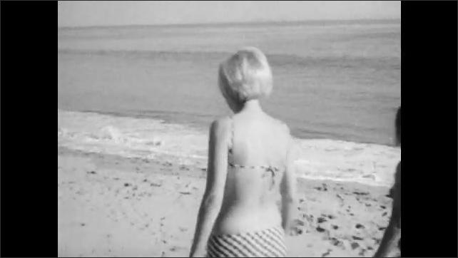 1960s: Girls in bikinis play volleyball on beach.  Girl ducks under net. Woman walk together on beach toward waves.