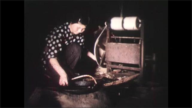 1950s: ASIA: lady turns wheel on silk loom. Lady prepares silk thread. Lady works loom