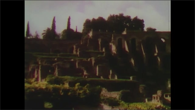 1950s: Large stone columns stand against clouds in sky. Ruins stand among tiered gardens and trees. Columns and ruins in Rome, Italy.