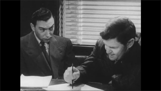 1950s: Two men sit at table, talk and argue, look at papers.