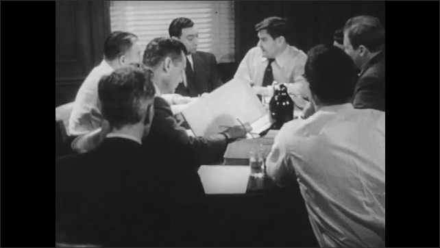 1950s: Men sit around table, talk. Workers file into factory.