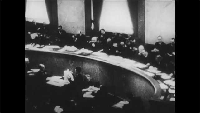 1950s: Groups of flags from different countries. Politicians meet. Group of people sit in a circle, talk. Group of people sit at tables, talk.