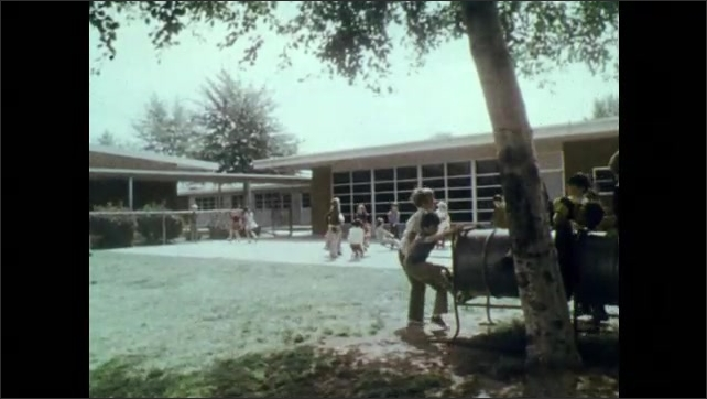 1970s: UNITED STATES: Merlinda School Sign. View across road to car park. Children in playground. Children play together. Girl plays hopscotch. Children climb bars