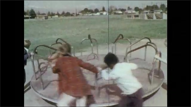 1970s: UNITED STATES: Toy bear plays drum. Girl walks home from school. Man sat on bench with dog. Children spin roundabout in park