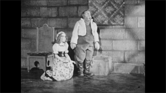 1940s: Puppet theater, castle, King stands by throne, talks, gestures. Father stands, daughter kneels, quivers, looks startled, Father pats her back.