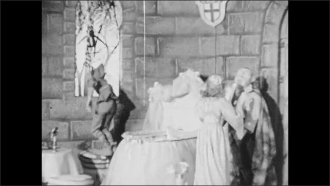 1940s: Puppet theater, castle, bird flies up to window. Rumpelstiltskin stands by crib, turns, raises hands, jumps up to window. Juliana talks, nods, turns to father.