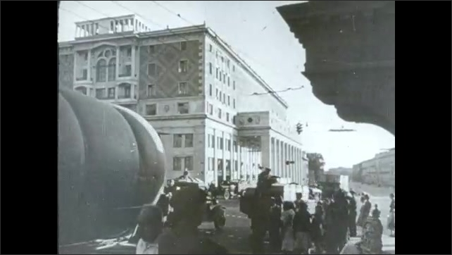 1940s: Russian soldiers march in military parade through Moscow. Traffic in city street. People crowd around newsstand with papers.