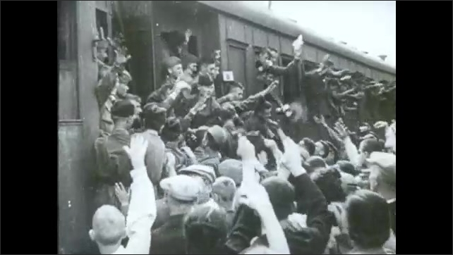 1940s: Officer eats food in caf??. Soldiers wave from outbound train to people at station.