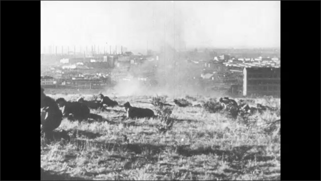 1940s: Men ride tank through factory. Men with rifles crawl over hills. Men with helmets and rifles train in field. Small rural village and windmill.