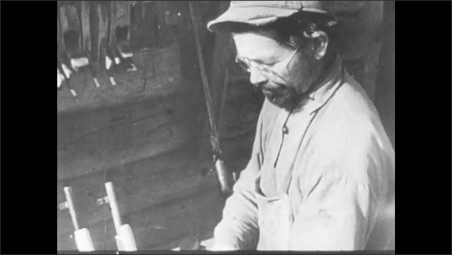 1940s: Men and women guerilla fighters talk. Man assembles rifle. Men assemble mobile machine gun cart.