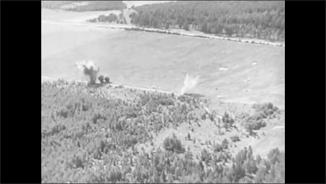 1940s: Pilot looks through bombing scope. Plane drops bombs. Bombs fall and explode on road.