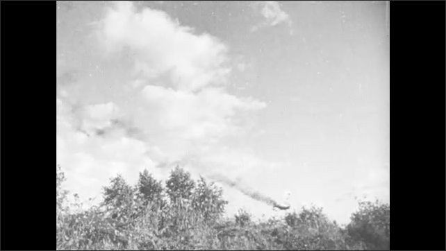 1940s: Smoke trails from damaged bomber. Bomber plane explodes on impact with ground. Soldiers examine plane wreckage. Soldiers march up rural road.