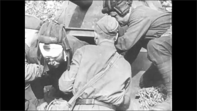 1940s: Surgeons operate on wounded soldier. Bloody uniform. Men drag wounded soldier from tank. Soldiers load wounded comrades into back of truck.