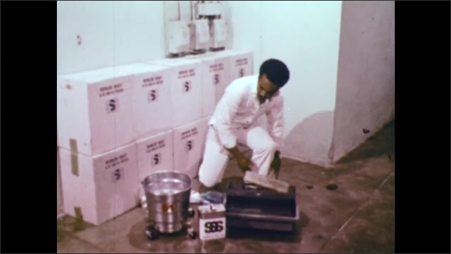1970s: UNITED STATES: SSS cleaning solution in container. Man presses out seal. Man wraps head in Turkish towel.