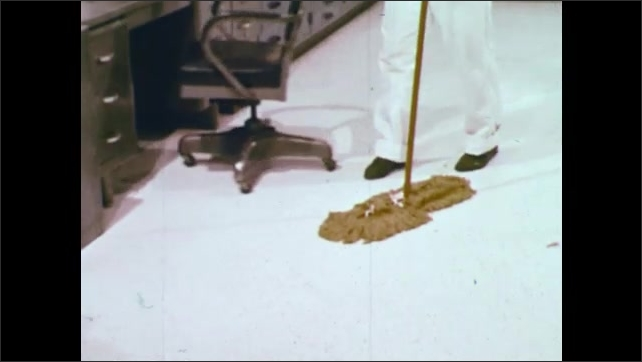 1970s: UNITED STATES: man shakes dust mop on floor. SSS dust mop. Chair under work station. Daily damp mopping with neutral detergent.
