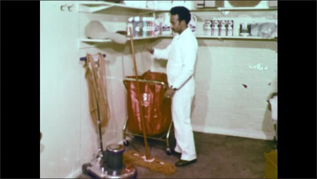 1970s: UNITED STATES: man sprays dust mop in cleaning cupboard. Man hangs up mop with face away from wall.