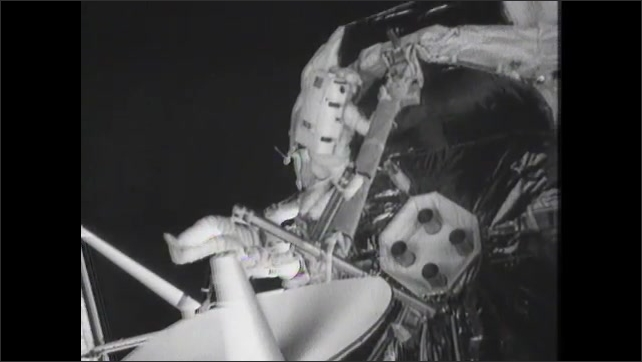 1980s: UNITED STATES: astronaut in foot restraint on EVA. Astronaut raises boom to full deploy position. Astronauts lock boom in position
