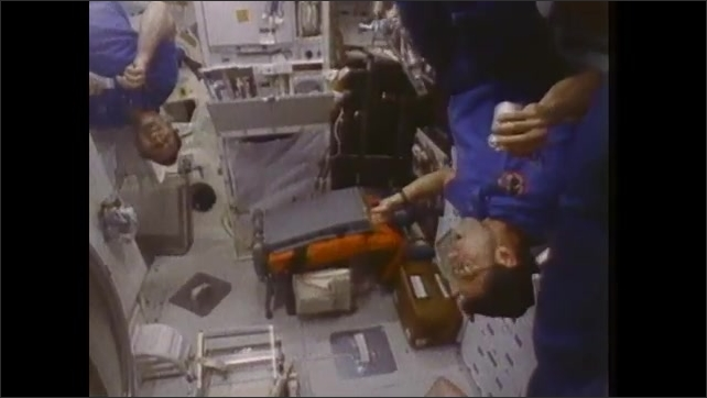 1980s: UNITED STATES: astronauts eat malted milk balls in space. Astronauts relax during meal