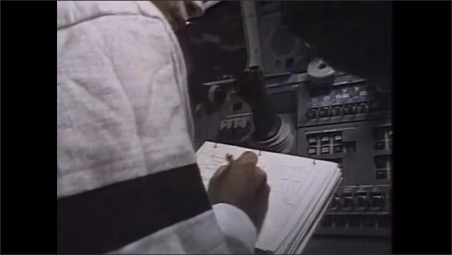 1980s: UNITED STATES: bright spot and flash during RCS burns. Astronaut with check list. Astronauts in cockpit