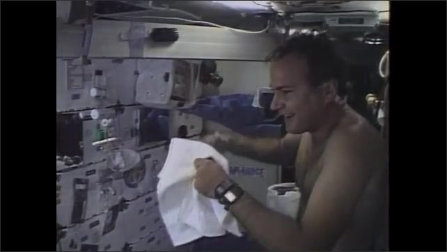 1980s: UNITED STATES: astronaut shampoos hair in space.