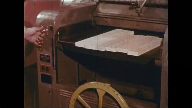 1960s: Man bends to adjust controls on machine.  Man turns on single surface planer.  Man feeds lumber into machine.