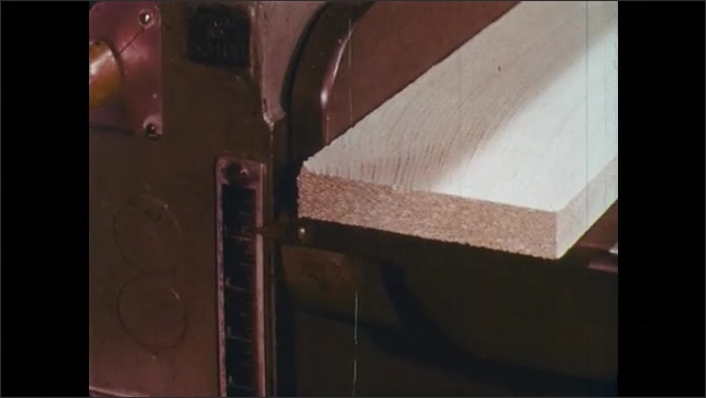 1960s: Piece of wood sits on single surface planer.  Pointer indicates ruler on machine.  Hand feeds lumber into machine.