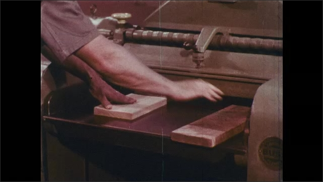 1960s: Boards come out of single surface planer.  Man picks up wood.  Man pulls lever.  Man feeds three boards end to end into machine.
