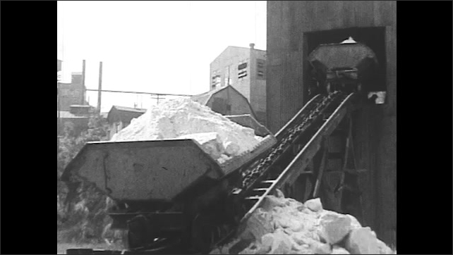 1930s: Train of sand moves to small warehouse. Train dumps sand. Sand on treadmill. Words explain sand is screened.