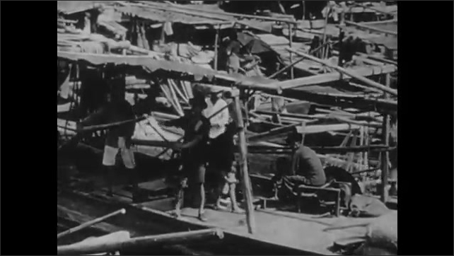 1940s: CHINA: view across Chinese harbour. Boats in Shanghai. Small boats in river sanpans. People on footbridge