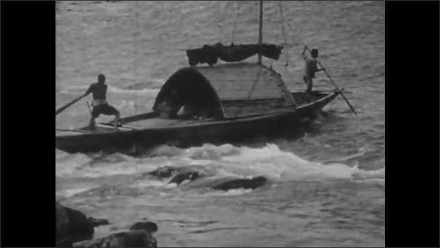 1940s: CHINA: sanpan travels inland up river. People on river bank. Man pushes boat off rocks
