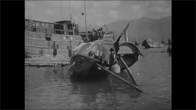 1940s: CHINA: sailor hoists sail on boat in China. Crowded harbour with sanpans and junks in China. Sail on boat.