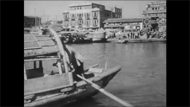 1940s: CHINA: sanpan boat carries hay and straw. Taxi cab boat. Rush hour on waterway in China. Sanpan carries coffin to burial ground up river.