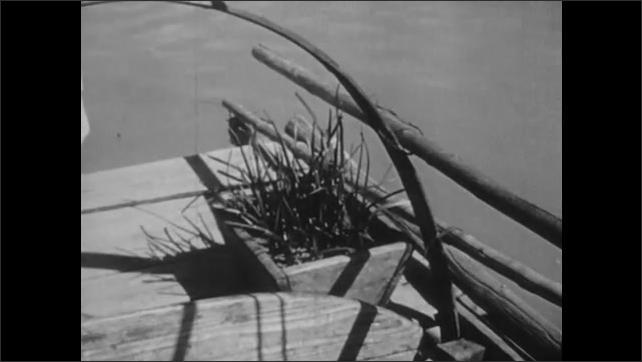 1940s: CHINA: man smokes pipe on sanpan boat deck. Lady tends flower garden on sanpan boat. Man sews fishing net.