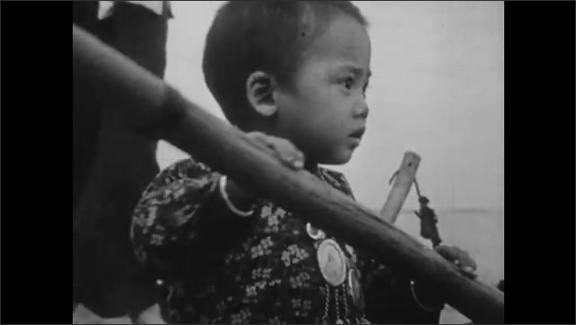 1940s: CHINA: children row sanpan boats. Lady smiles at child rowing. Baby with religious icons. Family fishing from sanpan boat.