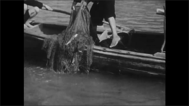 1940s: CHINA: family prepare fish for lunch. Man hauls in fishing net.