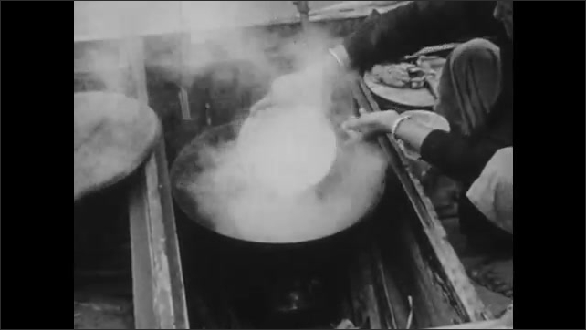 1940s: CHINA: lady prepares rice on sanpan boat. Lady cooks rice. Man catches fish in net. Boy and father pull fishing nets in.