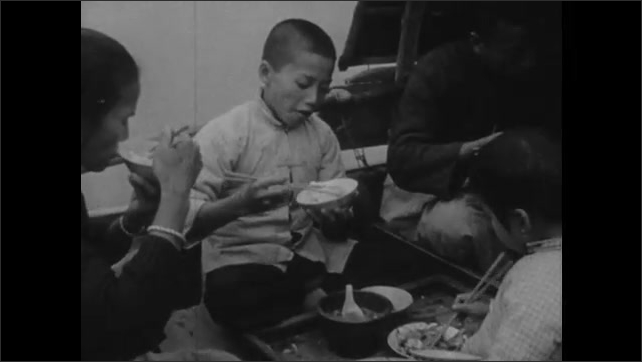 1940s: CHINA: fish in water on boat. Family eat fish, greens, and rice for lunch on sanpan. Family eat with chopsticks.