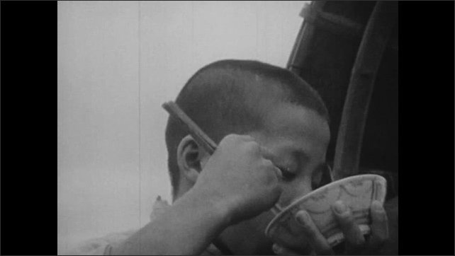 1940s: CHINA: boy eats rice from bowl with chopsticks. Family eat with chopsticks on sanpan boat