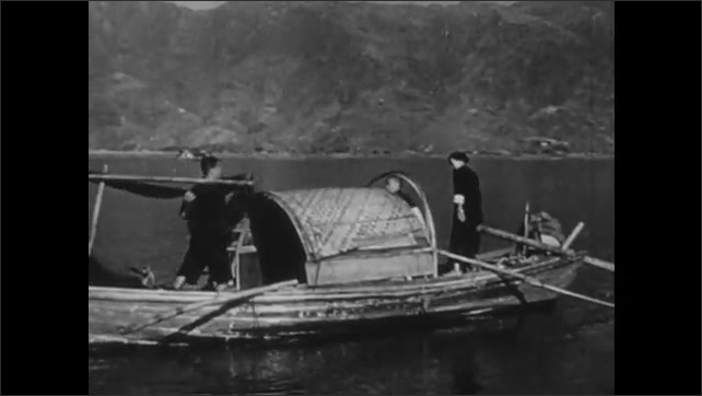 1940s: CHINA: man spreads nets to dry on sanpan boat. Family hang up nets on poles on boat.
