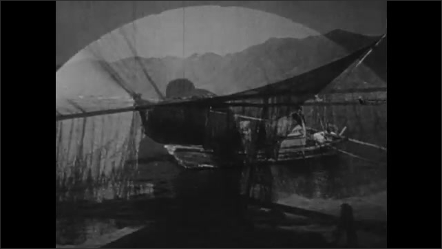1940s: CHINA: nets dry on fishing boat. Family row boat back home.
