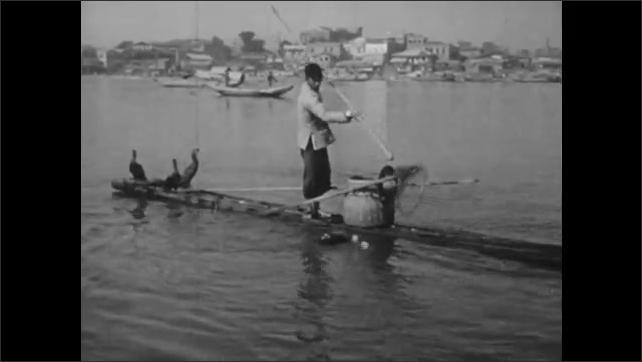 1940s: CHINA: lady on sanpan boat smiles. Family watch cormorant fisherman. Man rows sanpan boat.