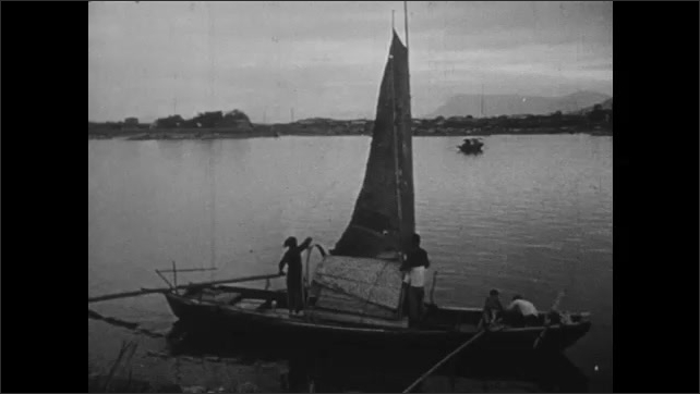 1940s: CHINA: Sanpan people row boats in China. Mountain and harbour view.