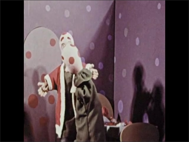 1960s: Two identical hand puppets have conversation in room as one lies on ground with blanket and mop on top of them. Puppet tries on red Santa coat as other puppet looks on.