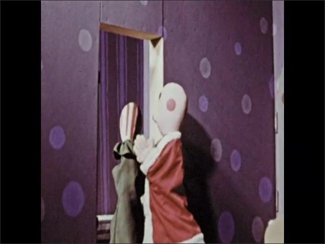 1960s: Hand puppet takes Santa Claus hat off other puppet. Two puppets leave bedroom having a conversation.