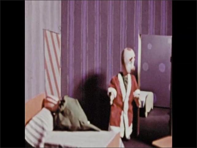 1960s: Hand puppet wearing Santa Claus coat talks to puppet sitting on bed. Puppet in Santa coat leaves room. Puppet sits on bed holding Santa hat.
